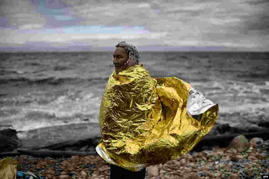 A man with a protective blanket around his shoulders stands on the beach as refugees and migrants arrive on the Greek island of Lesbos after crossing the Aegean Sea from Turkey. (AFP/Aris Messinis)