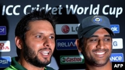 Pakistani cricket captain Shahid Afridi (left) with Indian captain Mahendra Singh Dhoni during a press conference at the Punjab Cricket Association Stadium in Mohali on March 29