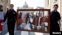Пример для каждого католика: два священника несут портреты двух святых. Ватикан готовится к главному празднику XXI века