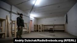 Дмитро Кондратьєв показує процес облаштування бомбосховища, куди під час артобстрілу приходили люди