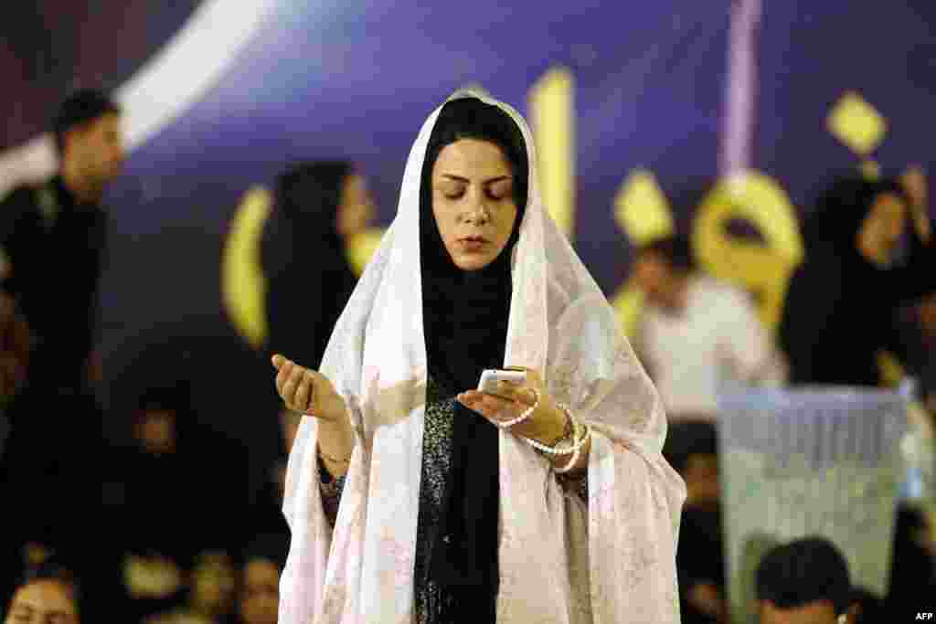 An Iranian woman holds her mobile phone as she prays at the Imam Khomeini grand mosque in the capital, Tehran. (AFP/Atta Kenare)