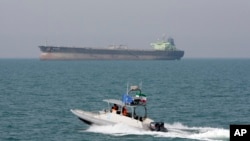 An Iranian Revolutionary Guard speedboat moves in the Persian Gulf while an oil tanker is seen in background. (file photo)