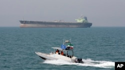 FILE-- In this July 2, 2012 file photo, an Iranian Revolutionary Guard speedboat moves in the Persian Gulf while an oil tanker is seen in background.