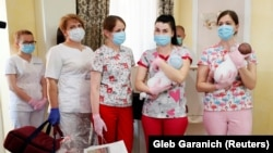 Nurses hold newborns during a ceremony to hand the babies over to their foreign parents in Kyiv on June 10.