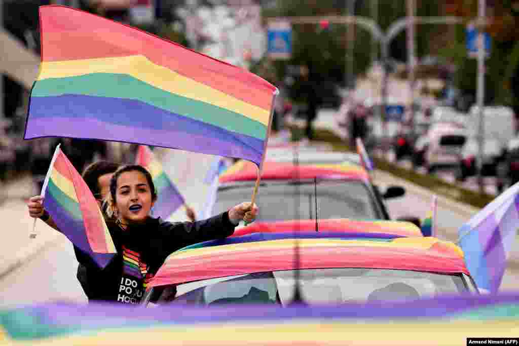 A woman waves rainbow flags as she takes part in the lesbian, gay, bisexual, and transgender pride parade in Pristina on October 12. (AFP/ Armend Nimani)