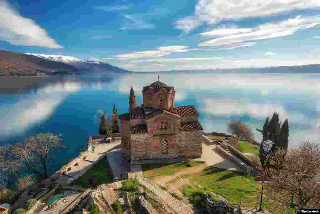 Kisha e Shën Gjonit Teolog në bregun maqedonas. Liqeni i Ohrit ndahet nga Maqedonia e Veriut dhe Shqipëria, dhe pranë tij ndodhen disa prej kishave më të vjetra sllave në Evropë. Më 1979, pjesa maqedonase e liqenit u përfshi në listën e Trashëgimisë Botërore të UNESCO-s.