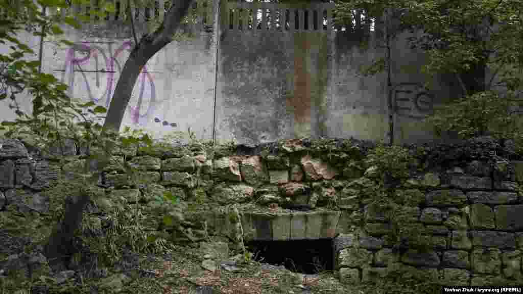 Бетонный забор стоит на старых строениях
