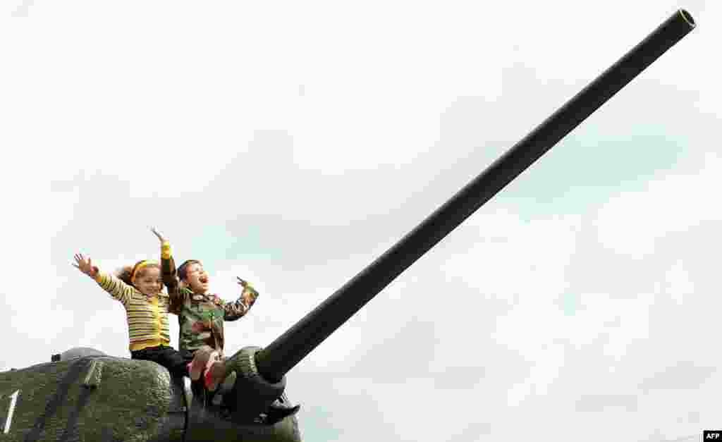 Armenia -- Children sit atop the World War II-era Soviet T-34 tank during Victory Day celebration in Yerevan, May 9, 2013