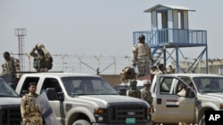 قوات أمن عراقية تقف أمام سجن البلديات ببغداد بعد نشوب حريق فيه