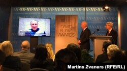 BBG CEO John Lansing (center) and RFE/RL President Thomas Kent (right), listen to recorded comments by RFE/RL Crimea journalist Mykola Semena at the 2016 David Burke Awards ceremony in Washington.
