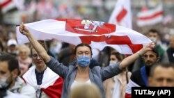 Демонстрант в маске для защиты от коронавируса машет старым белорусским национальным флагом во время митинга оппозиции в знак протеста против официальных результатов президентских выборов в Минске, Беларусь, 27 сентября 2020 года.