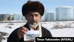 Местный экологический активист показывает снимки на фоне строящегося НПЗ в кыргызском городе Кара-Балта. 7 февраля 2013 года.