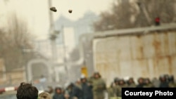 Iranian opposition supporters throw stones at riot policemen during clashes in Tehran on December 27.