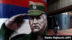 Žena sa zaštitnom maskom prolazi pored grafita s likom ratnog generala Vojske Republike Srpske Ratka Mladića, u Beogradu 12. novembra 2020.