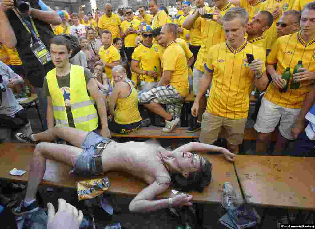 Shachko in front of Swedish football fans as she protests against prostitution during the UEFA Euro 2012 football championship in Kyiv.