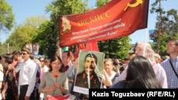 Қазақстанның Коммунистік партиясының мүшелері Жеңіс күні советтік билікті мадақтаған ту мен сурет көтеріп тұр. 9 мамыр, 2014 жыл