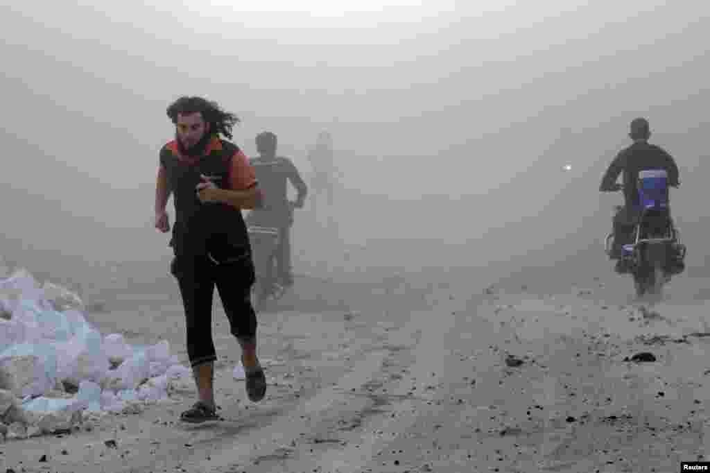 Residents run though dust after what activists said were air strikes carried out by the Russian Air Force in the rebel-controlled area of Maaret al-Numan in Idlib Province, Syria. (Reuters/Khalil Ashawi)