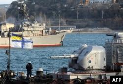 Корабель ВМС України «Славутич» стоїть на якорі перед мінним тральщиком ВМС Росії, патрулюючи гавань Севастополя, 10 березня 2014 року