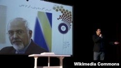 Wikipedia Senior Manager Arash Soleimani giving a speech at the 14th anniversary of Persian Wikipedia next to the image of Javad Zarif.December 2017