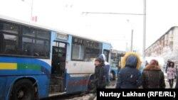 Автобусы на остановке общественного транспорта.