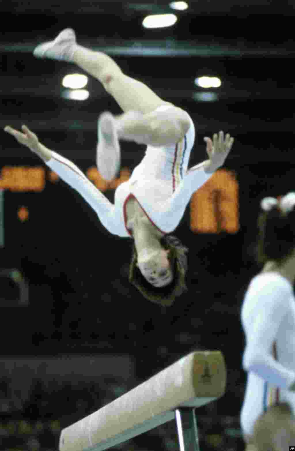 Румынская гимнастка Надя Команечи исполняет кувырок во время выступления, за которое она получит очередную идеальную десятку, на этот раз на балансире. Ее первые круглые 10 баллов были присуждены на Олимпиаде в Монреале в 1976 году. Она стала первой гимнасткой в истории, добившейся такого результата.