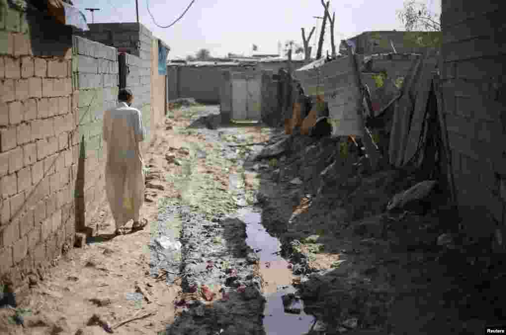 An Iraqi Shi'ite cleric walks through a poor neighborhood in the Al-Fdhiliya district.