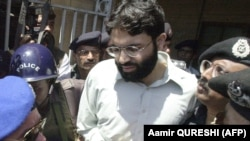 Pakistani police surround handcuffed Omar Sheikh as he comes out of a court in Karachi in 2002.