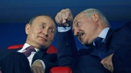 Russian President Vladimir Putin (left) and Belarusian President Alyaksandr Lukashenka speak in the stands during a ceremony in Minsk in June 2019.