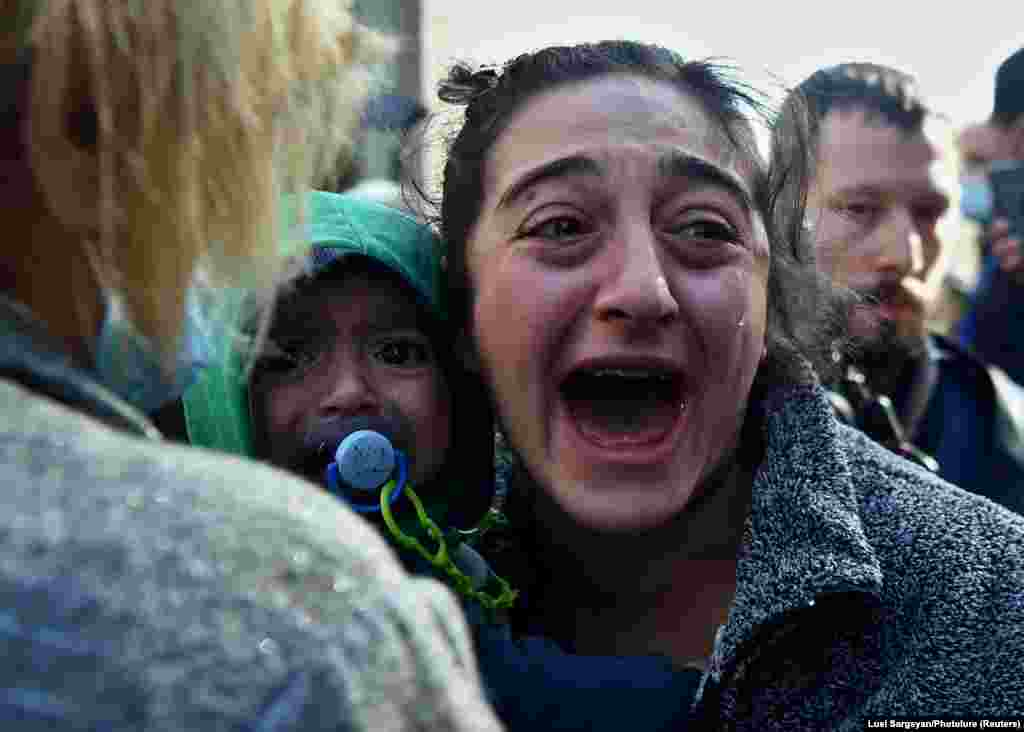 A woman holding a child reacts during an opposition rally to demand the resignation of Armenian Prime Minister Nikol Pashinian following the signing of a deal to end the military conflict over the Nagorno-Karabakh region, in Yerevan on November 11. (Lusi Sargsyan/Photolure via Reuters)
