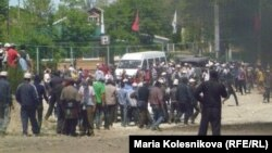 Protesters gather as smoke rises near the main point of confrontation with police on the main road to Kumtor gold mine on May 31, when clashes injured dozens of people.