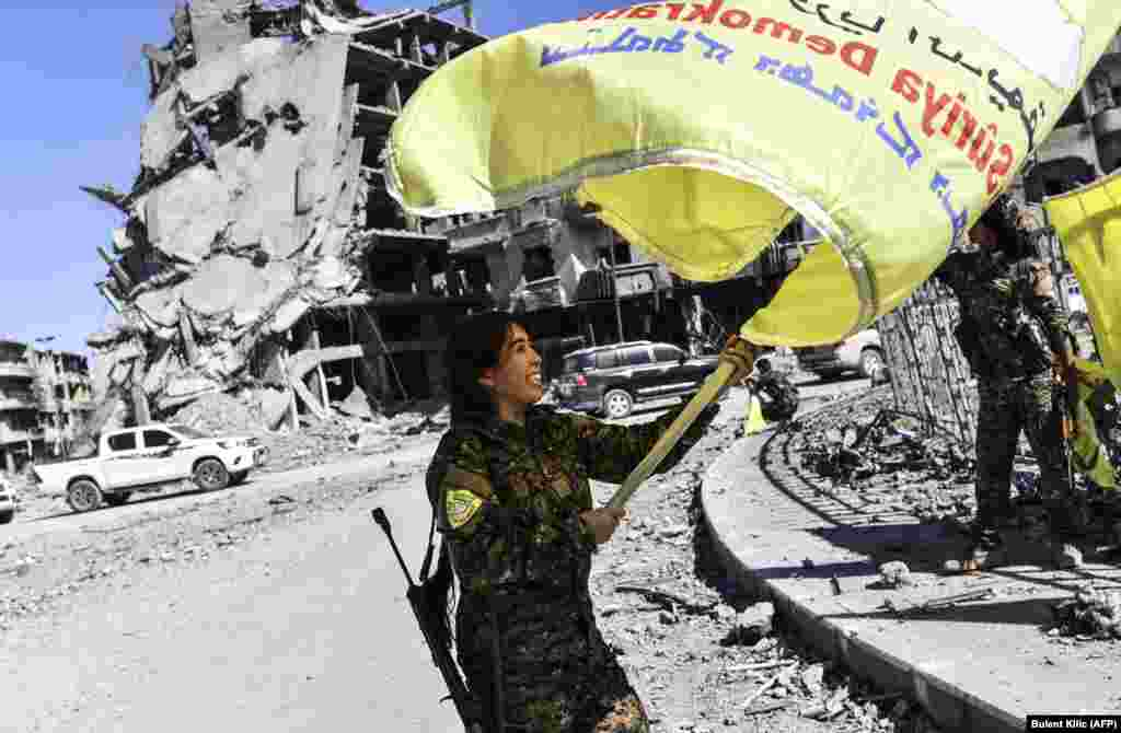 Rojda Felat, a Syrian Democratic Forces (SDF) commander, waves her group's flag at the iconic Al-Naim Square in Raqqa on October 17. U.S.-backed forces said they had taken full control of Raqqa from the Islamic State extremist group. (AFP/Bulent Kilic)