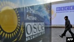Астанадағы ЕҚЫҰ саммиті жарнамасының жанынан өтіп бара жатқан адамдар. Астана, 2010 жылдың желтоқсаны.