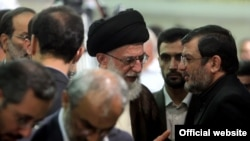 Iranian Supreme leader Ali Khamenei meets the father of Mohsen Rouholamini, undated.