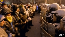 Ukraine -- Pro-EU Ukrainian protesters stand opposite riot policemen securing the area outside the presidential office in Kyiv, December 9, 2013