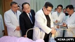 Kim Jong-Un (ortada) Şimali Koreyada xəsarət almış çinli turistə baş çəkir, arxiv fotosu