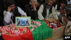د دولت خان مړي ته خلک ناست دي. تابوت یې د افغانستان په بیرغ پوښل شوی دی.