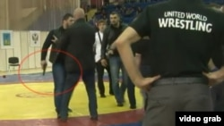 A screen grab from a YouTube video appears to show a man brandishing a gun during a melee that broke out during a wrestling match in Russia.