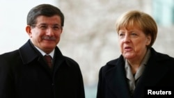 Germany -- German Chancellor Angela Merkel reacts next to Turkish Prime Minister Ahmet Davutoglu during a welcoming ceremony in Berlin, January 12, 2015