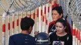 Уйгурские женщины проходят через контрольно-пропускной пункт, чтобы попасть на базар в Хотане в Синьцзян-Уйгурском автономном районе Китая.