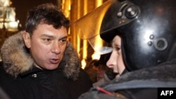 Boris Nemtsov speaks with a police officer on Triumph Square in Moscow on December 31, when he was arrested.