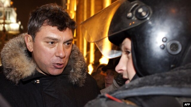 Boris Nemtsov (left) speaks with a police officer wearing riot gear on Moscow's Triumfalnaya Square on December 31.