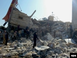 People gather near a destroyed building said to be a Medecins Sans Frontieres (MSF) supported hospital in Marat al Numan, Idlib, Syria, in February 16.