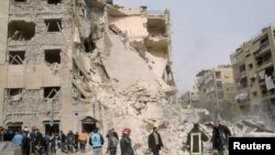 "Security personnel and civilians gather at the site of a large blast in a neighborhood of Aleppo on January 18. State television blamed the explosion on ""terrorists,"" a term used to describe antigovernment rebels."