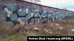 Граффити «Камуфляж» на заборе в дачном кооперативе на мысе Фиолент