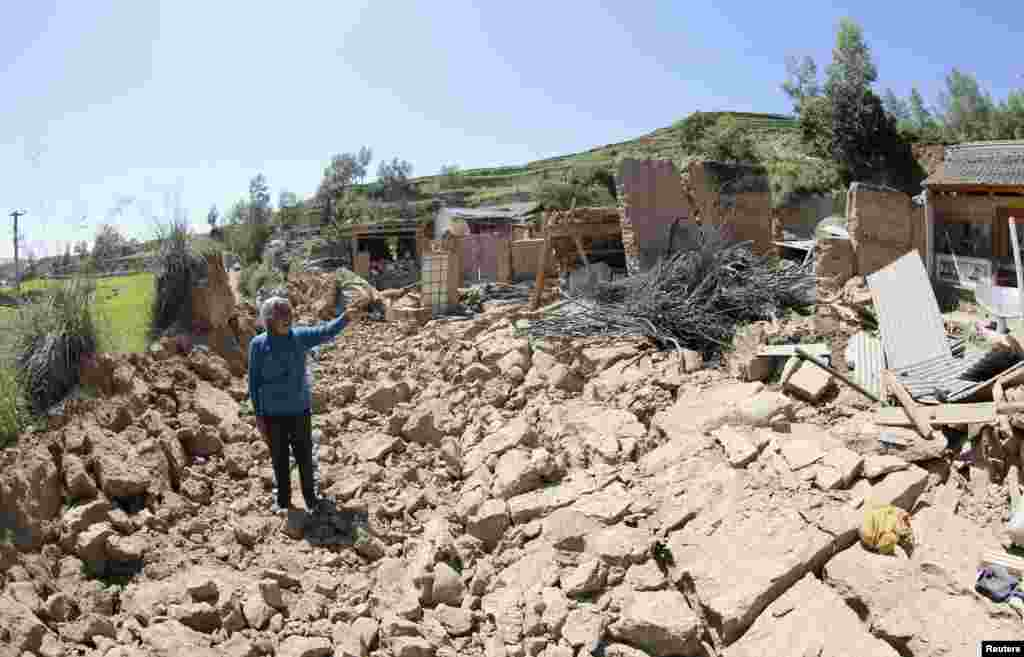 A woman points at her collapsed home after a strong earthquake rocked Gansu Province.