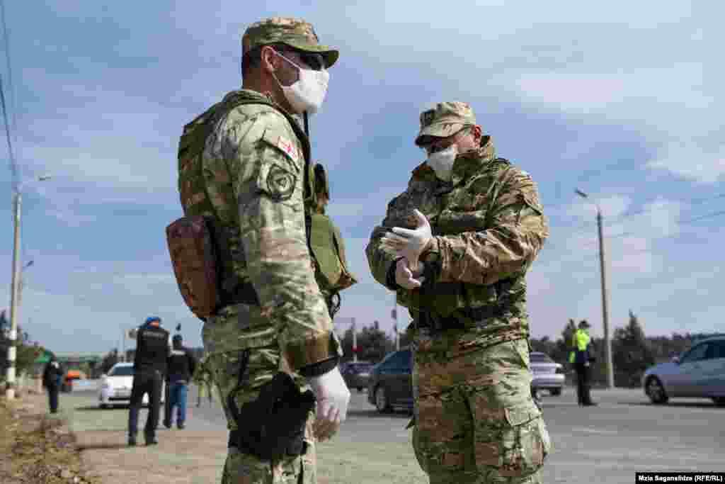 სამხედრო მოსამსახურეები მარლის პირბადით და ხელთათმანებით, საკონტროლო პუნქტთან, ლილოში.