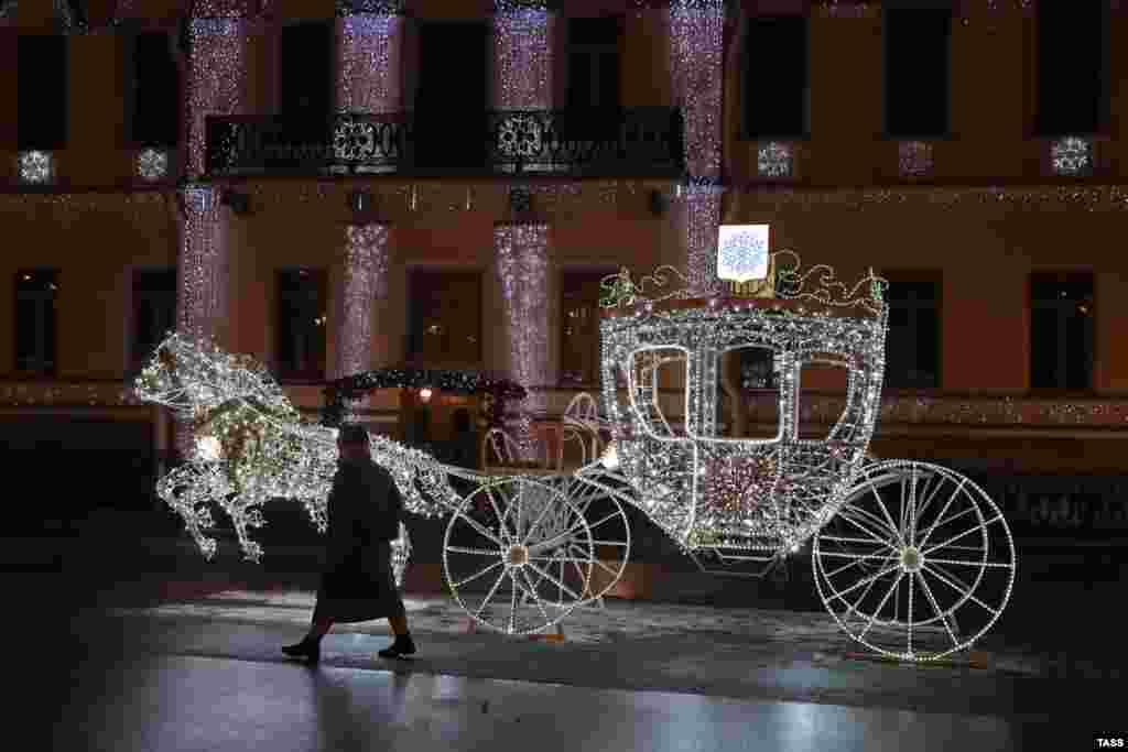 Коледна светлинна инсталация, представляваща каляска с коне е издигната на Университетската крайбрежна улица в Санкт Петербург.