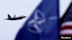The U.S. and NATO flags flutter as a U.S. Air Force F-22 Raptor fighter jet flies over the military air base in Siauliai, Lithuania, on April 27.