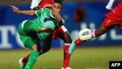 لاعب المنتخب العراقي بكرة القدم أحمد ياسين يسدد الكرة بإتجاه مرمي منتخب عُمان