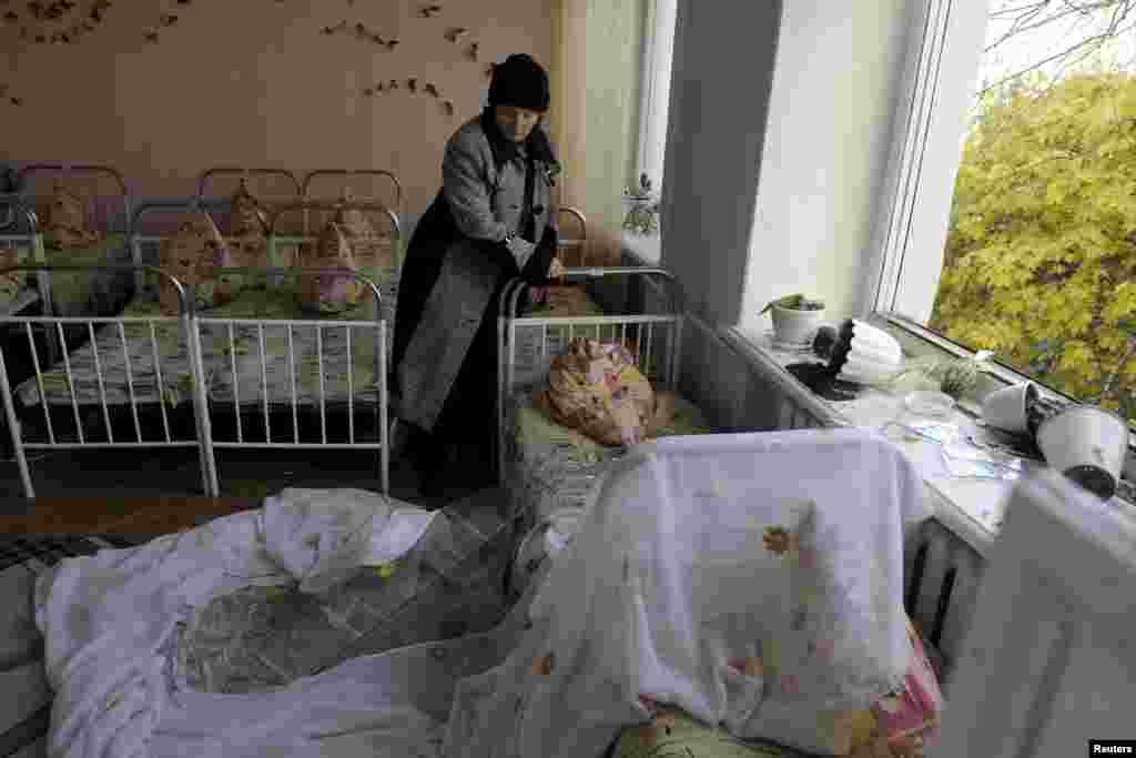 Жінка прибирає сміття з ліжок у дитсадку